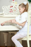 Little girl at a white Grand piano. Beautiful, elegant little girl holding hands on the keys of a white Grand piano. Girl playing at the Christmas concert in royalty free stock photography