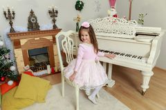 Little girl at a white Grand piano. Cute little girl in beautiful pink dress and a rose in her hair.She put her hand on the keys of a vintage white piano stock photo