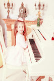 Little girl at a white Grand piano. Stock Image