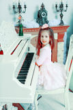 Little girl at a white Grand piano. Royalty Free Stock Photo