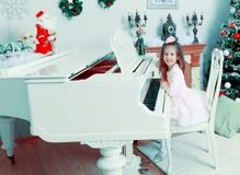 Little girl at a white Grand piano. Royalty Free Stock Photography