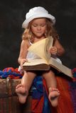 Little girl in a white  hat leafs through a large book on a dark Royalty Free Stock Image