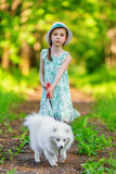 Little girl with white pomeranian spitz Stock Images