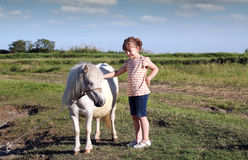 Little girl and white pony horse Stock Photography