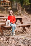 Little girl with a white puppy. A puppy in the hands of a girl. Little smiling girl having fun with puppy in outdoors cafe stock photo