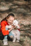 Little girl with a white puppy. A puppy in the hands of a girl. Little smiling girl having fun with puppy outdoors in the park stock photography