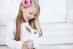 Little girl and white rabbit Stock Photos