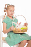 Little girl with a white rabbit in  basket easter eggs Royalty Free Stock Images