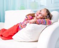 Little girl on a white sofa royalty free stock photos