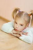 Little girl in white sweater lying Royalty Free Stock Images