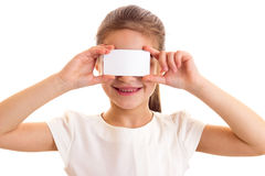 Little girl in white T-shirt holding white card Stock Images