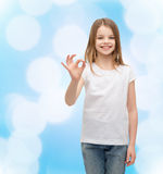 Little girl in white t-shirt showing ok gesture Stock Photo