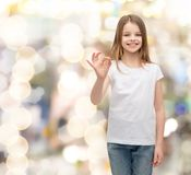 Little girl in white t-shirt showing ok gesture Royalty Free Stock Image