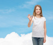 Little girl in white t-shirt showing ok gesture Stock Photos