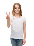 Little girl in white t-shirt showing peace gesture Stock Photos