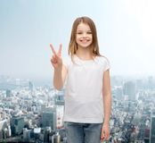 Little girl in white t-shirt showing peace gesture Royalty Free Stock Photography