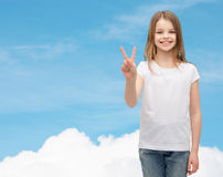 Little girl in white t-shirt showing peace gesture Stock Photo