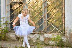 A little girl in a white T-shirt and skirt learns to dance on the street near the window of an old house stock photos
