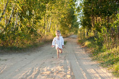 A little girl in a white traditional сhemise running  Stock Photo