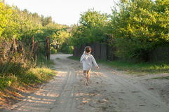 A little girl in a white traditional сhemise running Stock Images