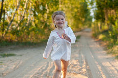 A little girl in a white traditional сhemise running in a scenic early autumn landscape Stock Photo