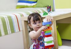 Little girl who builds castles with plastic cubes Stock Photos