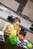 The little girl who drink water while eating in the kitchen Royalty Free Stock Image