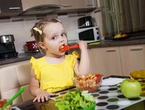 Little girl who eat healthy food in the kitchen Stock Image