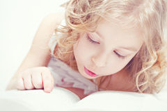 Little girl who loves to read. Portrait of little adorable girl with a book Stock Photography