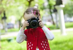 Little girl who takes pictures with a photo camera in park Royalty Free Stock Photos