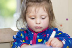 Little girl whose face  is smudged with paint Royalty Free Stock Images