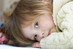 Little girl whose face and sweater is smudged with paint Stock Image