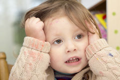 Little girl whose face and sweater is smudged with paint Stock Photography