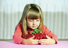 Little girl with wild strawberries, Stock Photo