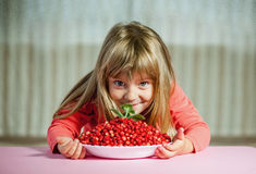Little girl with wild strawberries, Royalty Free Stock Photos