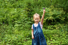 Little girl with a wildflower in the forest Stock Images