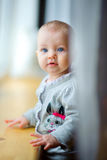 Little girl is by the window Royalty Free Stock Image