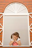 Little girl in the window Royalty Free Stock Photography