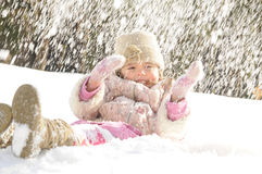 Little girl winter. The little girl lays on a snow, on her throw a snow in the winter Stock Photos