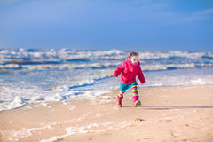 Little girl at winter beach Stock Photos