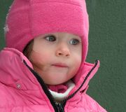 Little girl in Winter clothes. Portrait of sweet little girl dressed in warm, pink Winter clothes including hat and zipped quilted jacket Royalty Free Stock Images