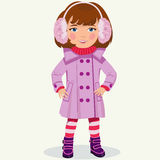 Little girl in winter clothes. Girl in a winter coat and fur headphones Stock Images