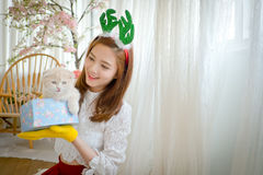 Little girl with winter clothes holding Christmas gift box, Royalty Free Stock Photo