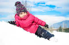 Little girl in winter clothes laying in snow waving and smiling Royalty Free Stock Photos