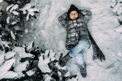 A little girl in winter clothes lying on a snowy meadow surround stock photography