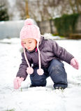 Little girl in winter clothes is playing in snow with her winter Stock Photos