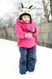 Little girl in winter clothes is playing in snow with snow on he Stock Image