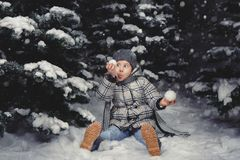 A little girl in winter clothes playing with snow on a snowy mea stock photography