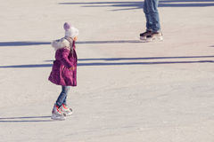 Little girl in winter clothes skating on ice rink Stock Photo