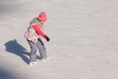 Little girl in winter clothes skating on ice rink Stock Photography
